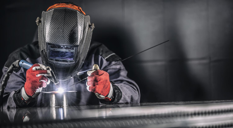 Welder industrial worker welding with argon machine.